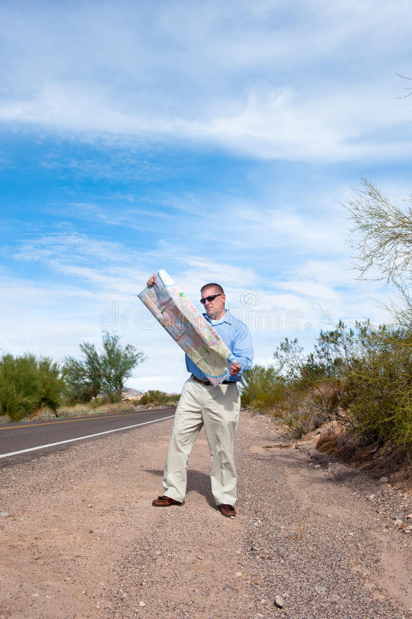 Man on deserted road reading map. A man stands along a deserted road reading a roadmap stock photo