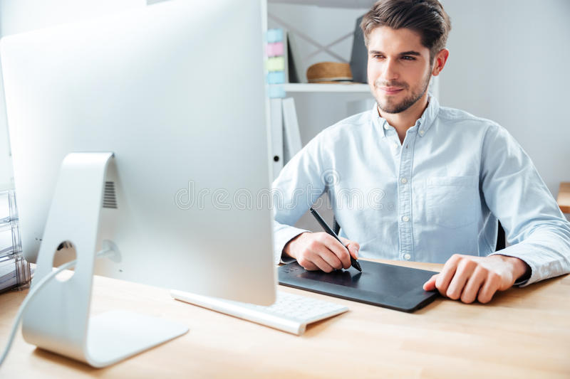 Man designer working using computer and graphic tablet at workplace. Happy young man designer working using computer and graphic tablet at workplace stock photos