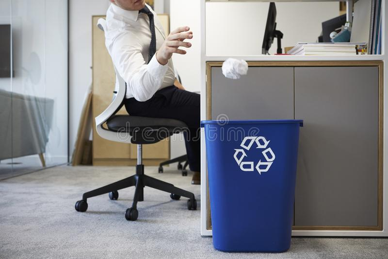 Man at desk throwing screwed up paper into recycling bin stock photo