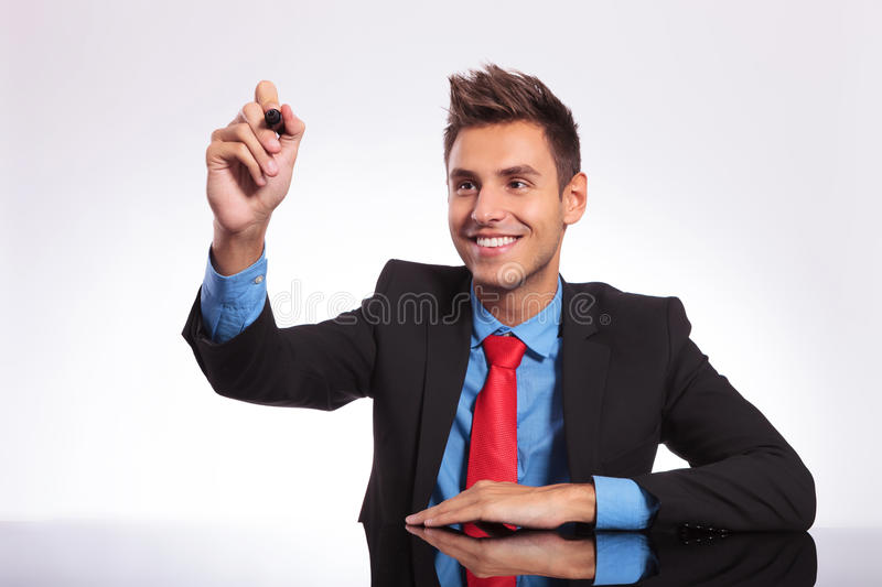 Man at desk writes on imaginary screen. Young business man sitting at the desk and writing something on an imaginary screen while smiling stock photo