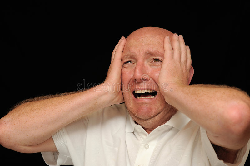 Man in despair. A bald man holding his head in, his face showing deep despair. Black background stock photo
