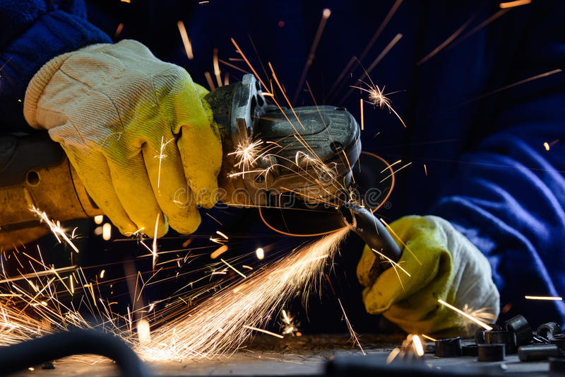 Man det bitande stålröret med en vinkelmolar producera varma gnistor royaltyfria bilder