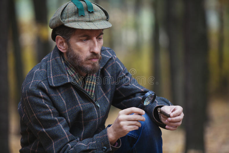 Man detective with a beard exploring tree fragment. Imposing man detective with a beard wearing a cap and a plaid jacket considers through magnifying glass royalty free stock images