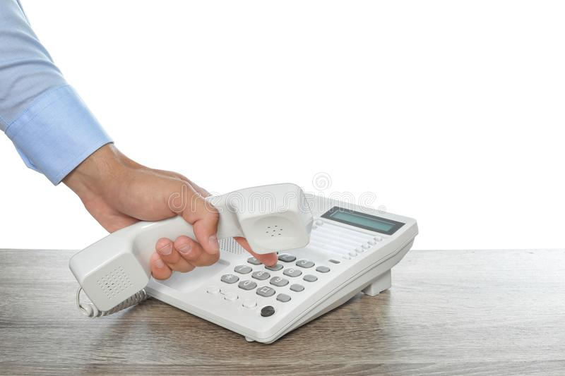 Man dialing number on telephone at table stock image