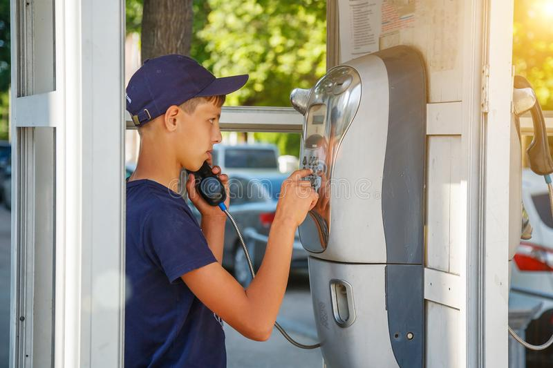 A man dials a phone number in a phone booth.  royalty free stock photography