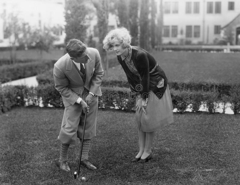 Man die aan vrouw spreken terwijl het golfing (Alle afgeschilderde personen leven niet langer en geen landgoed bestaat Leverancie stock afbeelding