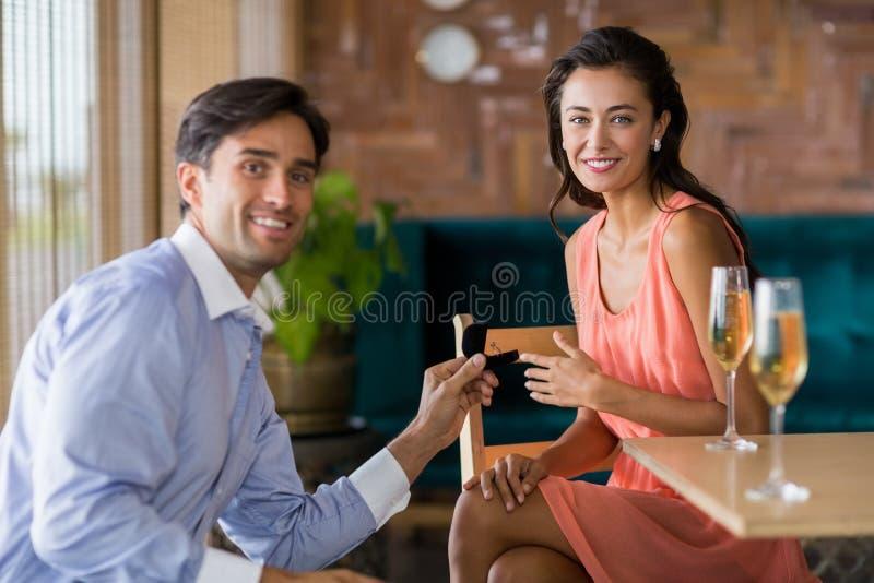 Man die aan vrouw voorstellen die verlovingsring aanbieden stock afbeeldingen