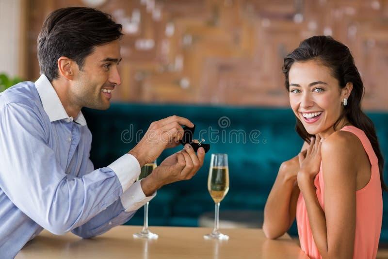 Man die aan vrouw voorstellen die verlovingsring aanbieden royalty-vrije stock fotografie