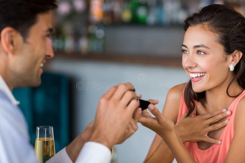 Man die aan vrouw voorstellen die verlovingsring aanbieden stock foto