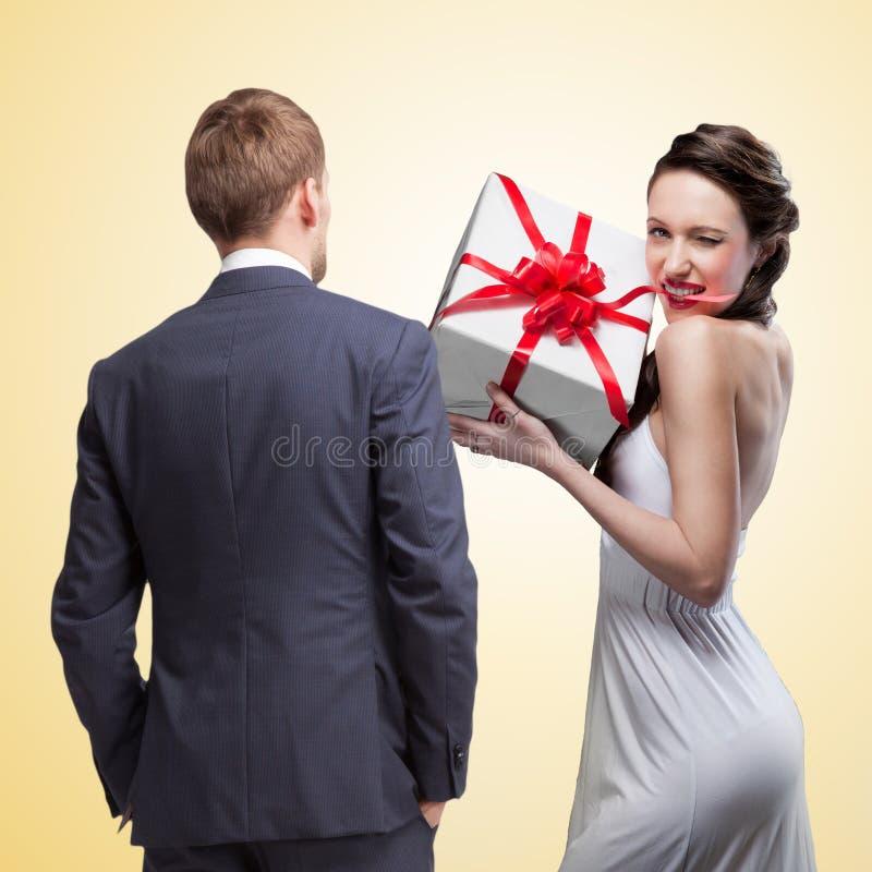 Download Man Die Bij Het Glimlachen Van De Gift Van De Vrouwenholding Kijken Stock Afbeelding - Afbeelding bestaande uit document, decoratie: 39112591