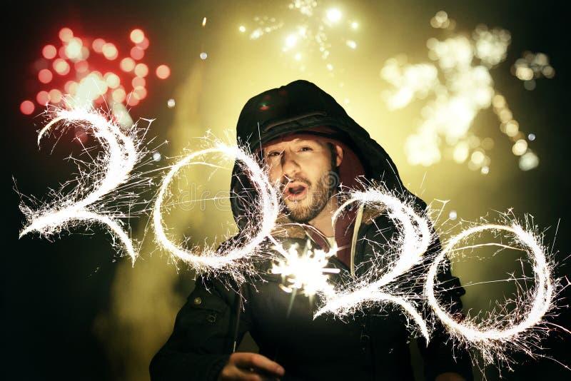Man die de Ouderdom van het Nieuwjaar viert met vuurwerk en de cijfers 2020 schrijft met een sparkler tijdens een lange blootstel royalty-vrije stock foto's