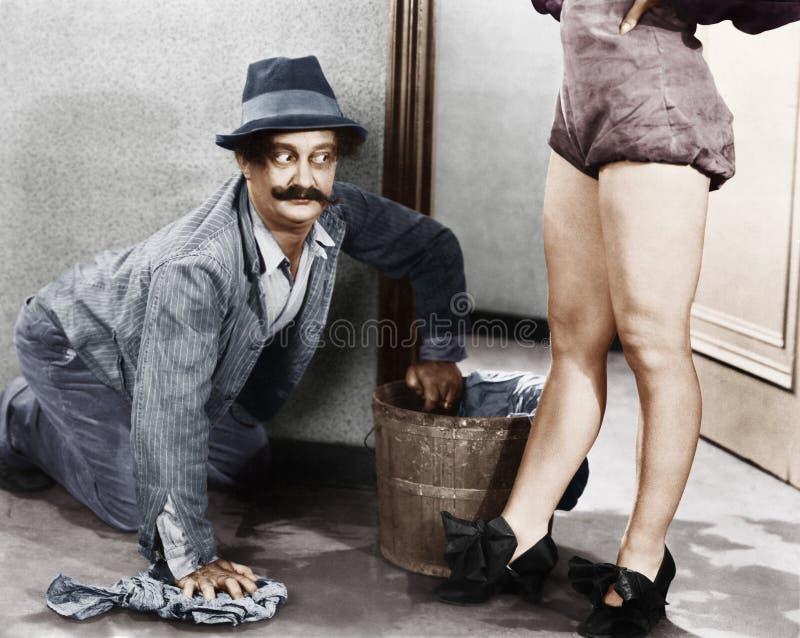 Man die de vloer schoonmaken die de benen van een vrouw bekijken (Alle afgeschilderde personen leven niet langer en geen landgoed royalty-vrije stock foto's