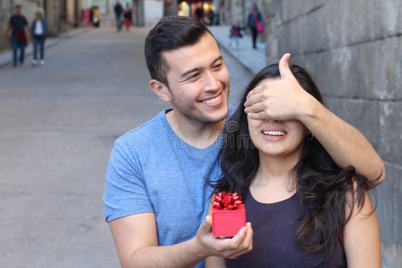 Man die een heden geven aan een schitterende vrouw stock foto
