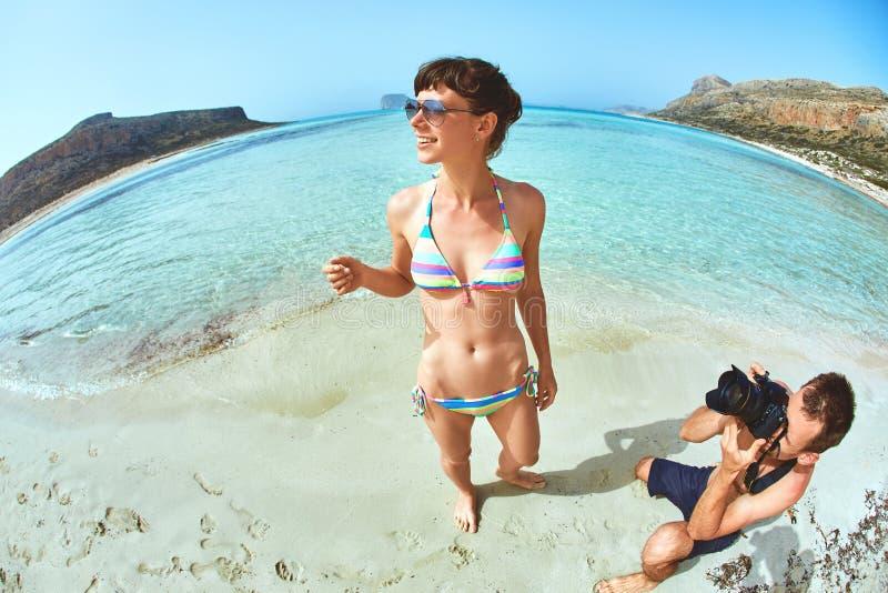 Man die een vrouw op het strand fotograferen royalty-vrije stock fotografie
