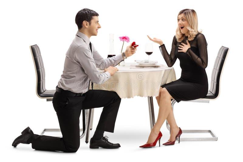 Man die en met een ring aan een vrouw bij een dinerlijst knielen voorstellen stock foto's