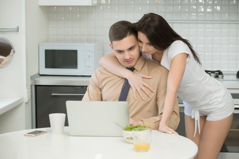 Man die in formele slijtage in keuken, vrouw werken die hem omhelzen royalty-vrije stock afbeelding