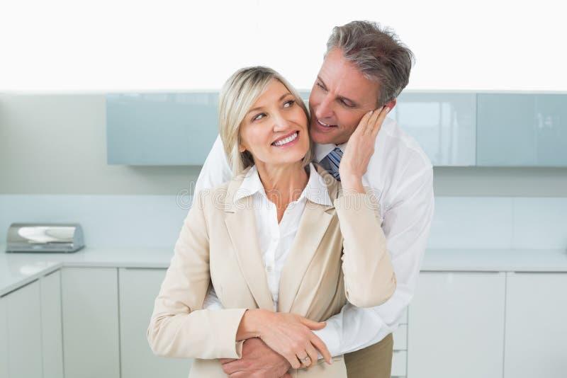 Man die gelukkige vrouw van erachter in keuken omhelzen royalty-vrije stock foto's