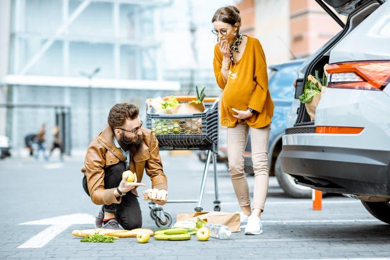 Man die jonge zwangere vrouw helpen dichtbij de supermarkt stock fotografie