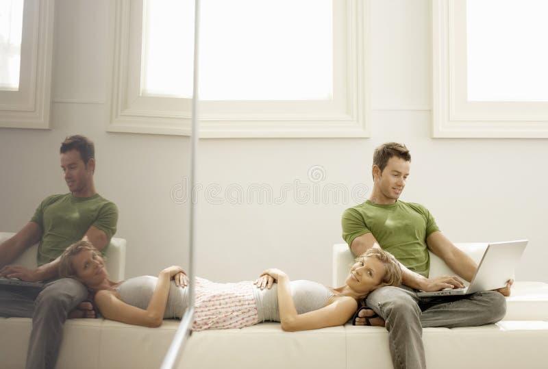 Man die Laptop met Vrouw het Liggen op Zijn Overlapping met behulp van stock foto