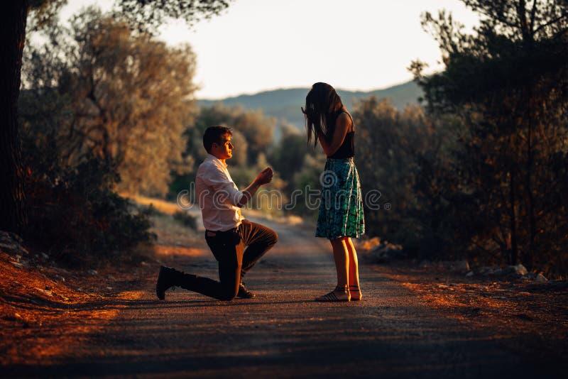 Man die in liefde een verraste, geschokte vrouw voorstellen om hem bij zonsondergang te huwen Voorstel, overeenkomsten en huwelij stock afbeelding