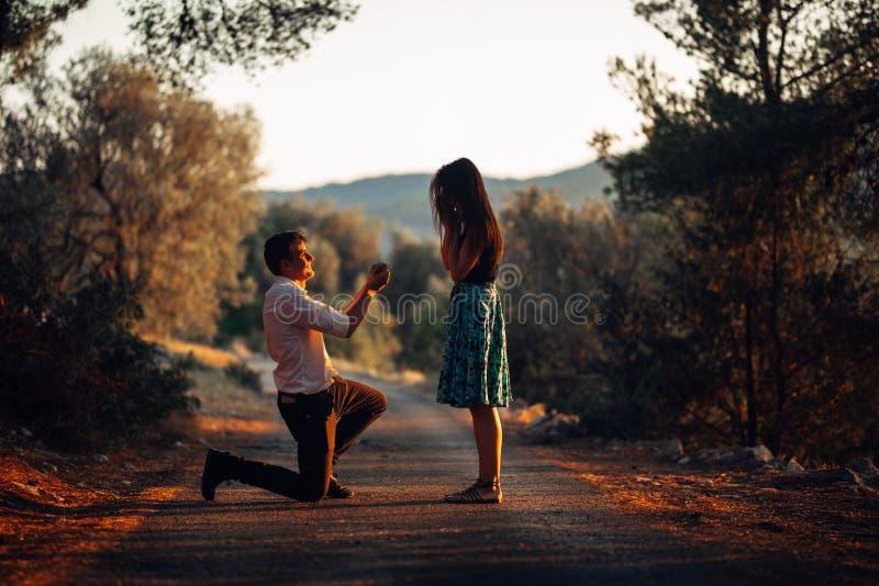 Man die in liefde een verraste, geschokte vrouw voorstellen om hem te huwen Voorstel, overeenkomsten en huwelijksconcept betrotha stock afbeelding