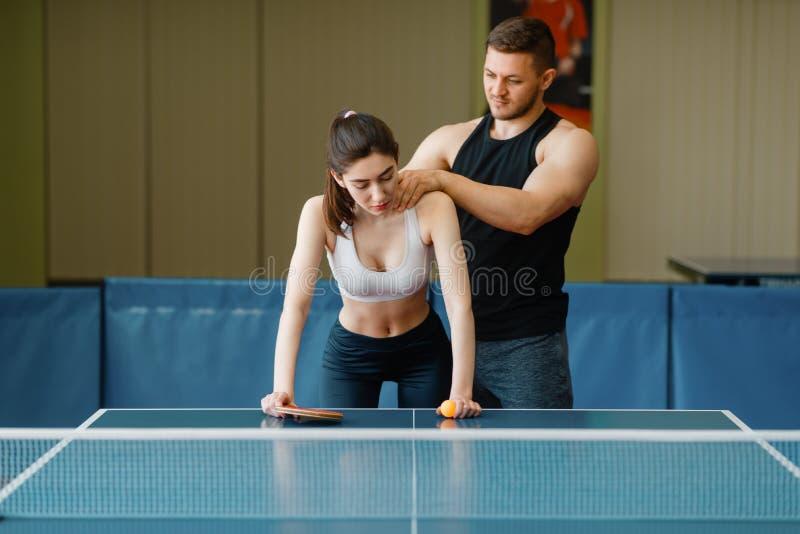 Man die massage aan vrouw, pingpong opleiding doen royalty-vrije stock afbeelding