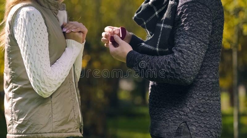 Man die met verlovingsring vrouw vragen om hem in de herfstpark, verrassing te huwen stock foto's