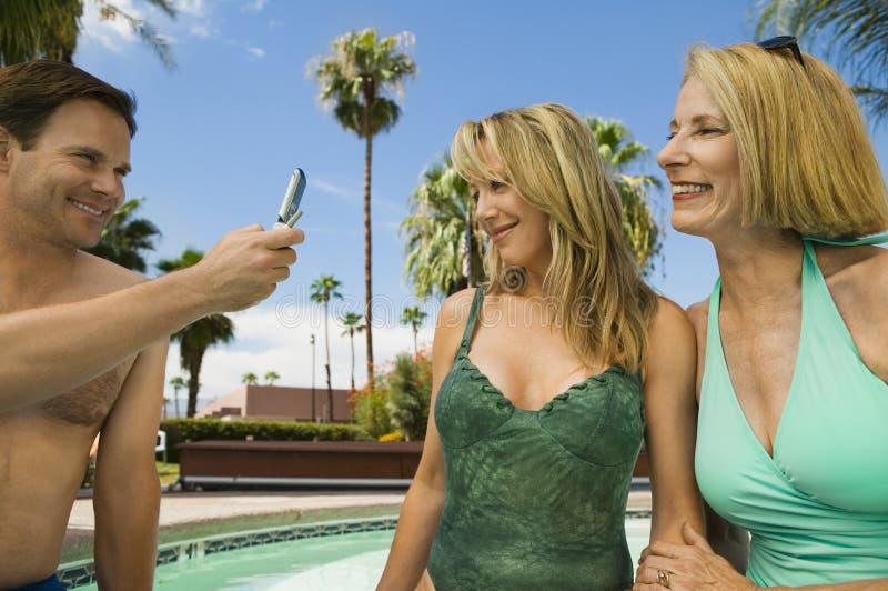 Man die mobiele telefoon met behulp van die twee vrouwen fotograferen door zwembad. stock afbeeldingen