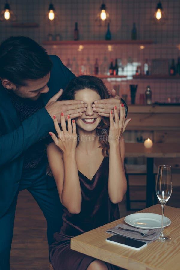 man die opgewekte vrouw verrassen bij lijst door haar ogen met handen te behandelen royalty-vrije stock foto's