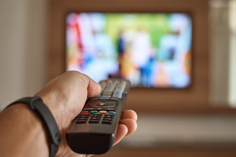 Man die tv kijkt in de kamer en schakelt kanalen over met behulp van de afstandsbediening in zijn hand stock foto