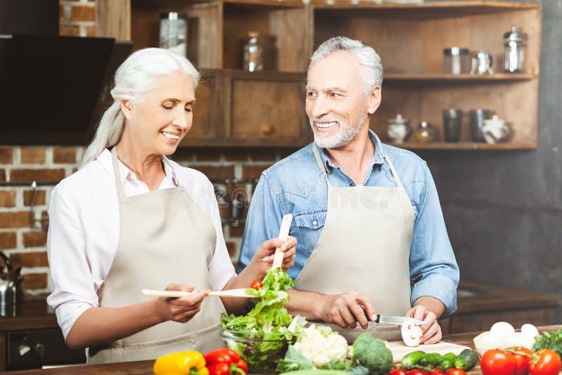 Man die vrouw bekijken die salade voorbereiden stock fotografie