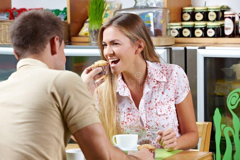 Man die vrouwenbeet van muffin geeft stock afbeeldingen