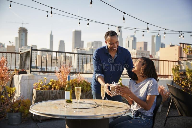 Man die Vrouwengift geven aangezien zij op Dakterras met Stadshorizon op Achtergrond vieren royalty-vrije stock fotografie