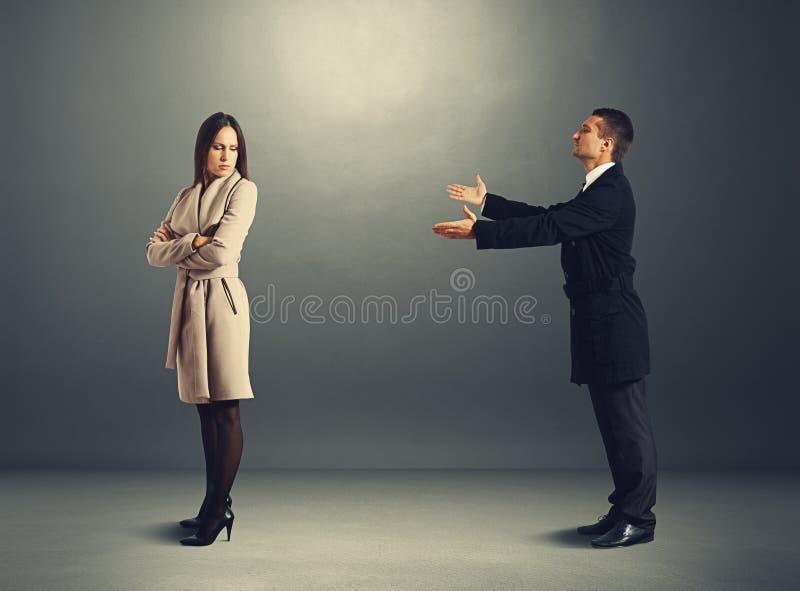 Man die zich aan beledigde vrouw verontschuldigen stock afbeeldingen