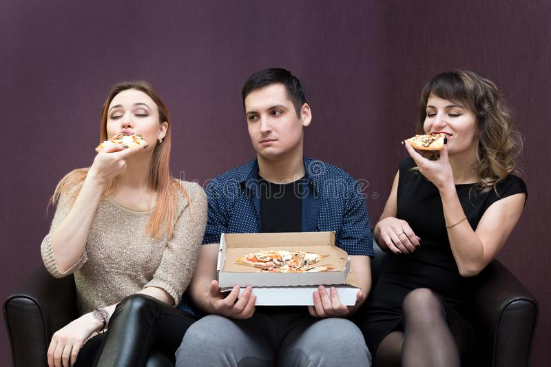 Man dieting looks like girlfriends eat pizza. A men because of illness can eat pizza jealous girls stock image