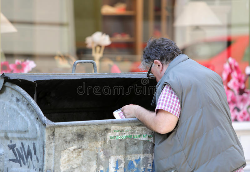 Man digging into a bin. Sofia, Bulgaria - June 10, 2015: A man is digging into a recycle bin in a main street in Sofia. Years after joining the EU many royalty free stock images