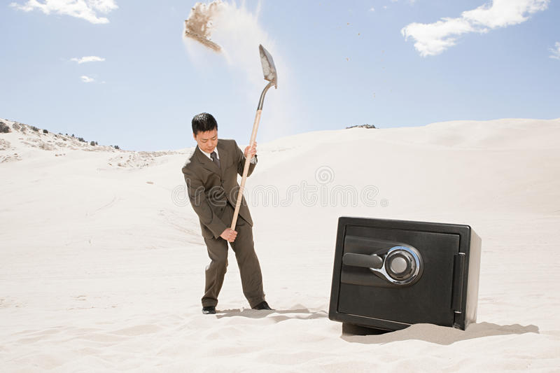 Man digging by safe in desert royalty free stock photo