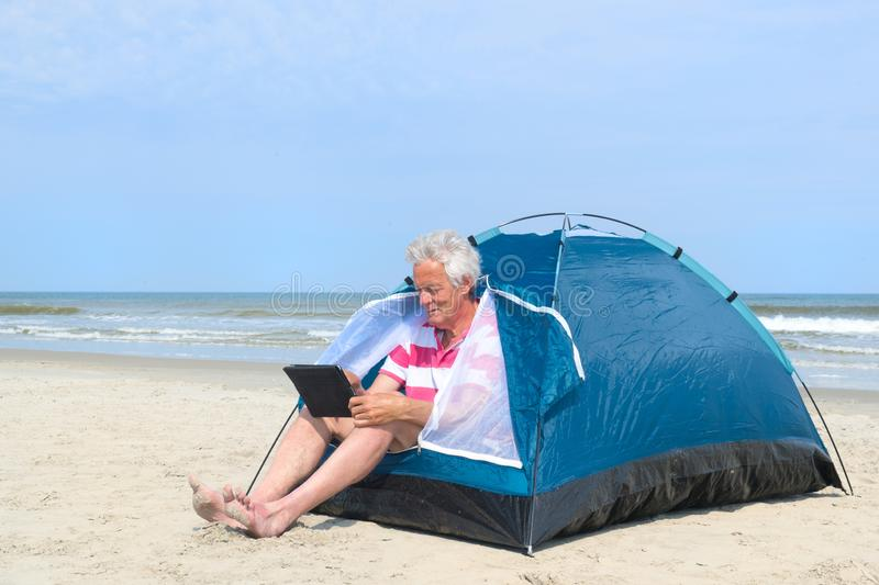 Man with digital tablet camping in shelter at the beach royalty free stock image