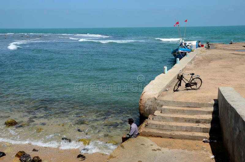Man dips feet in water at beach pier with fishing vessel near steps in Jaffna Sri Lanka. Jaffna, Sri Lanka - February 19, 2017: A sri Lankan fisherman dips his stock images