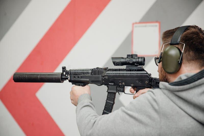 Man directs firearm gun pistol at target firing range or shooting range.  royalty free stock photos