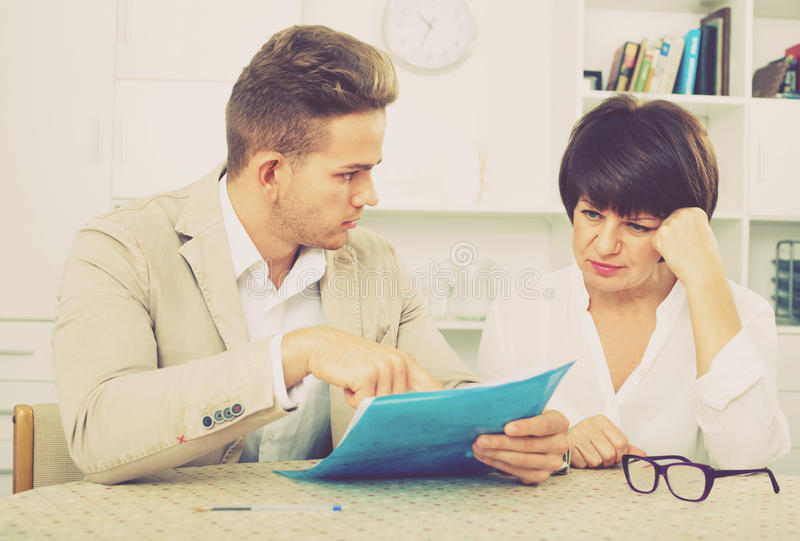 Man discusses correctness of paperwork with fellow worker royalty free stock photo