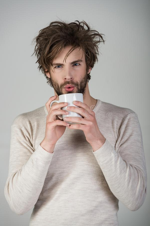 Man with disheveled hair drink mulled wine. Morning with coffee or milk. Insomnia, refreshment and energy. Sleepy guy with tea cup on grey background. Cold and stock image