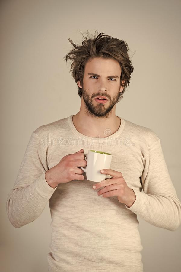 Man with disheveled hair drink mulled wine. Sleepy guy with tea cup on grey background. Cold and flu, single. Insomnia, refreshment and energy. Morning with stock images