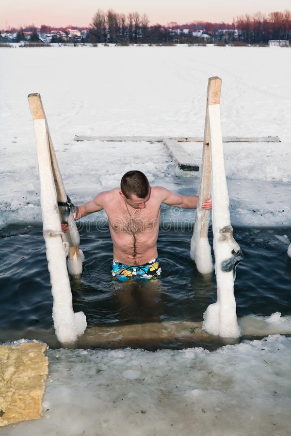 A man diving in the ice-hole on the Lake in winter
