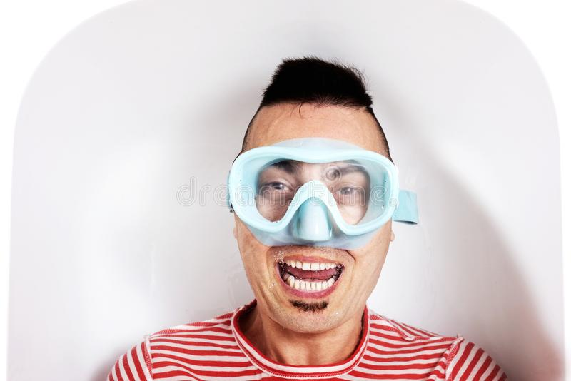 Man with a diving mask in the water of a bathtub royalty free stock images
