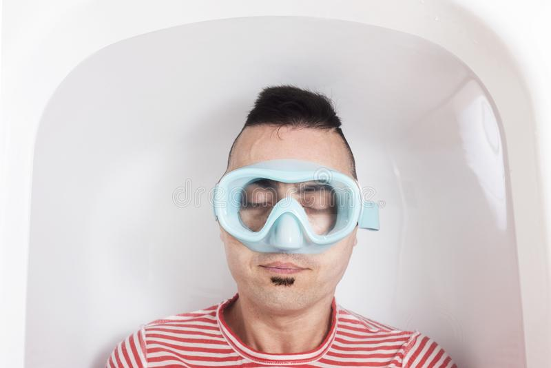 Man with a diving mask in the water of a bathtub royalty free stock image