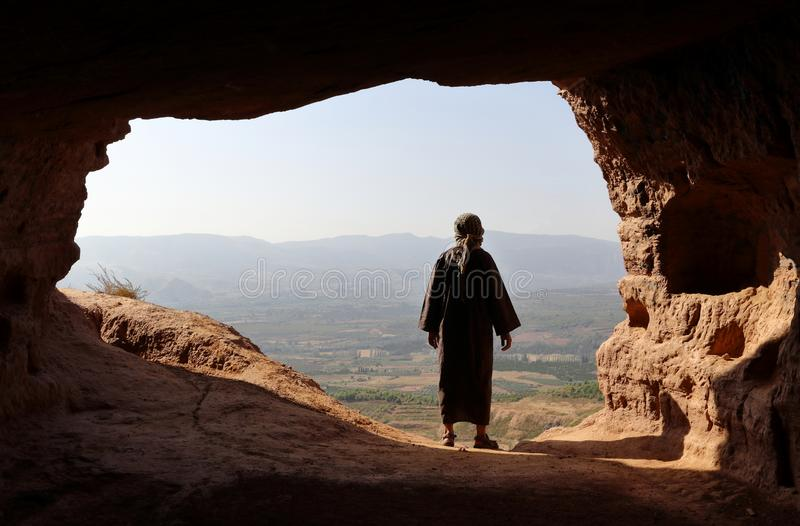 MAN WITH DJELLABA AND PALESTINIAN SCARF LOOKING TO THE VALLEY FROM A HIGH CAVE stock photo