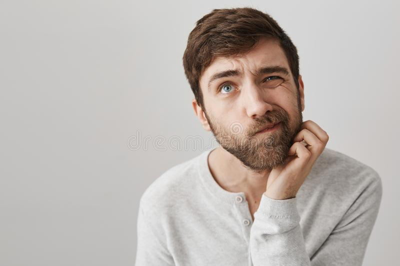 Man do not know how to solve problem. Indoor shot of clueless troubled european guy looking up and squinting, scratching royalty free stock photography