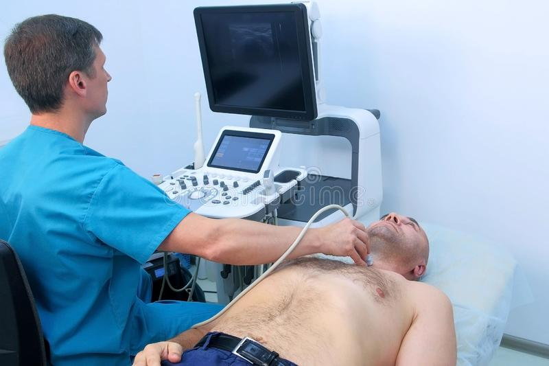 Man doctor examining man`s patient thyroid gland using an ultrasound scanner. Scanning of thyroid gland at ultrasound sanner device machine in hospital to men royalty free stock images