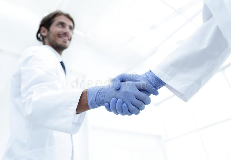 Man doctor shakes hand with another doctor in hospital stock photography